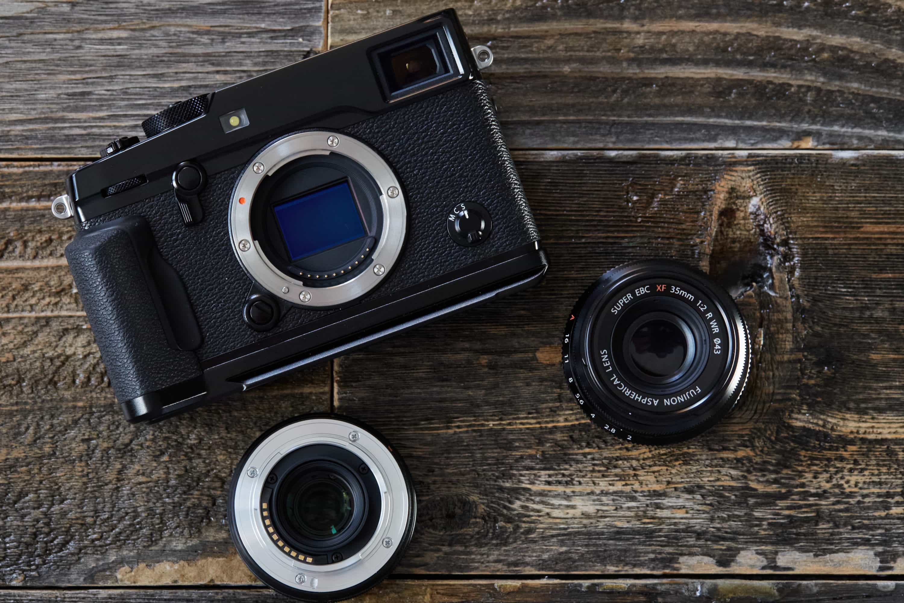 Fujifilm X-Pro2 camera and two Fuji lenses on wood background