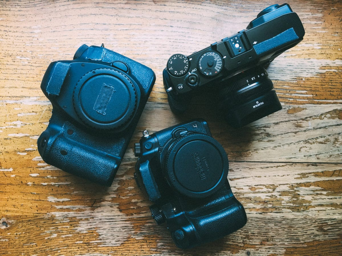 three cameras on wood background
